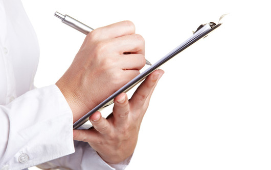 Hand Filling Out Checklist On Clipboard With A Pen