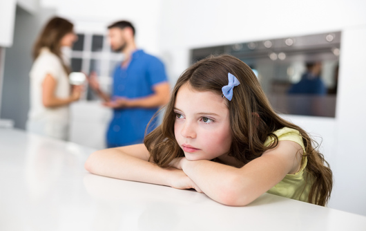 Sad Girl Leaning On Table Against Arguing Parents At Home