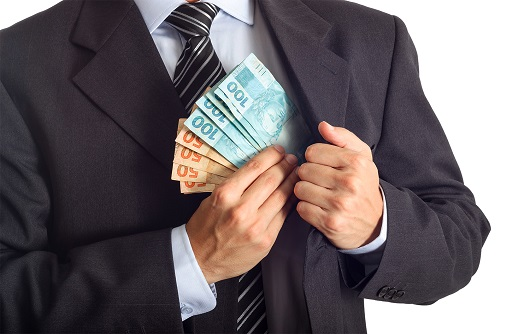 Businessman In A Suit Putting Money In His Pocket Isolated On White Background